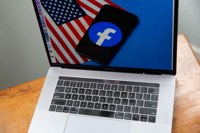 Facebook logo and US flag on a laptop screen