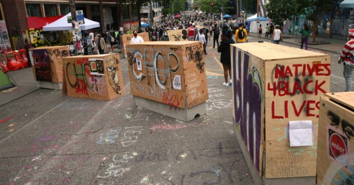SEATTLE, WA - JUNE 19: Barricades erected by the city several days ago divide up the CHOP zone on June 19, 2020 in Seattle, Washington. The concrete barriers, wrapped in plywood for painting, were installed to protect the free speech zone while still allowing one lane of traffic to get through. Nevertheless, protesters have blocked off entrances to traffic. (Photo by Karen Ducey/Getty Images)