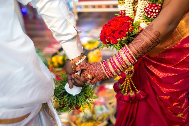 A bride and groom hold hands during a wedding