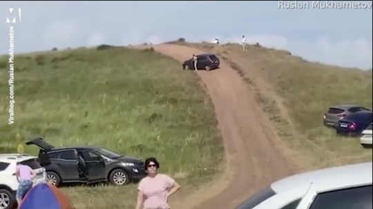 Runaway car speeds down a hill and misses picnickers by inches after driver gets out without pulling the handbrake
