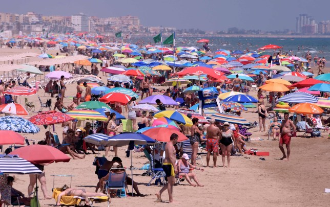 People enjoy a day at the Nord Beach in Gandia, near Valencia on July 1, 2020. - The European Union reopened its borders to visitors from 15 countries but excluded the United States, where coronavirus deaths are spiking once again, six months after the first cluster was reported in China. (Photo by JOSE JORDAN / AFP) (Photo by JOSE JORDAN/AFP via Getty Images)
