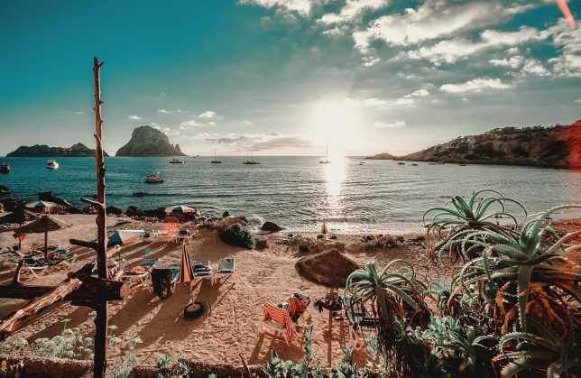 Picturesque scenery idyllic landscape photography like postcard of empty Cala d'Hort Beach, Es Vedra cliff view, yachts moored in serene Mediterranean Sea waters. Ibiza Island. Balearic Islands. Spain