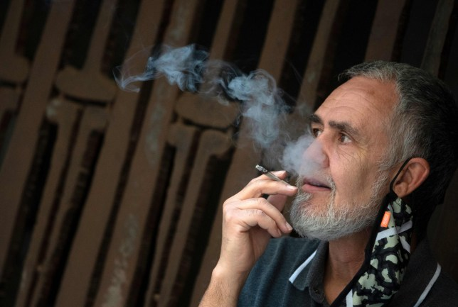 A man smokes a cigarette in a street of Valencia on August 13, 2020. - A ban on smoking on streets and restaurant terraces when social-distancing cannot be guaranteed came into effect today in Spain's northwestern region of Galicia, with other areas mulling similar restrictions to curb the spread of the coronavirus. (Photo by JOSE JORDAN / AFP) (Photo by JOSE JORDAN/AFP via Getty Images)