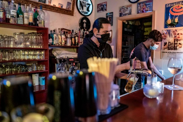 A bartender pours a beer at a bar in Berlin's Prenzlauer Berg district on October 10, 2020. - Stolz, along with other bar owners in Berlin, has challenged local authorities over the re-introduction of a curfew for bars in the capital, which are, from October 10 onwards, forbidden to operate between 11 PM and 6 AM. (Photo by JOHN MACDOUGALL / AFP) (Photo by JOHN MACDOUGALL/AFP via Getty Images)