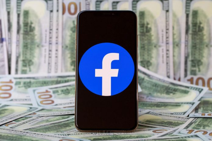 Facebook logo on a smartphone screen against a backdrop of $100 bills.