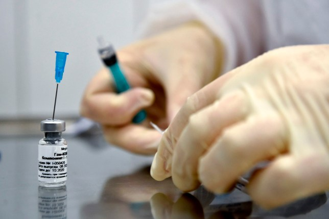 A nurse prepares to inoculate a volunteer with Russia's new coronavirus vaccine