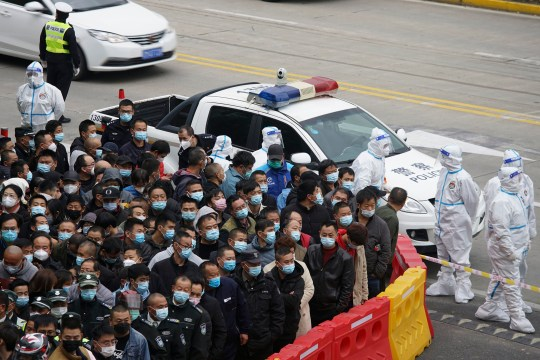 Security workers in protective suits stand by as workers wearing face masks to help curb the spread of the coronavirus gather for COVID-19 testing at the Shanghai Pudong International Airport in Shanghai, Monday, Nov. 23, 2020. Chinese authorities are testing millions of people, imposing lockdowns and shutting down schools after multiple locally transmitted coronavirus cases were discovered in three cities across the country last week. (AP Photo)