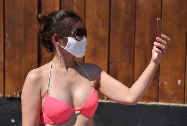 SOUTHEND-ON-SEA, ENGLAND - JUNE 25: A woman wearing a face mask takes a selfie as crowds of people gather on the beach on June 25, 2020 in Southend-on-Sea, England. The UK is experiencing a summer heatwave, with temperatures in many parts of the country expected to rise above 30C and weather warnings in place for thunderstorms at the end of the week. (Photo by John Keeble/Getty Images)