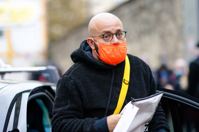 PARIS, FRANCE - SEPTEMBER 30: A guest wears glasses, a black fluffy winter coat with a hood, an orange protective face mask, outside Kenzo, during Paris Fashion Week - Womenswear Spring Summer 2021, on September 30, 2020 in Paris, France. (Photo by Edward Berthelot/Getty Images)