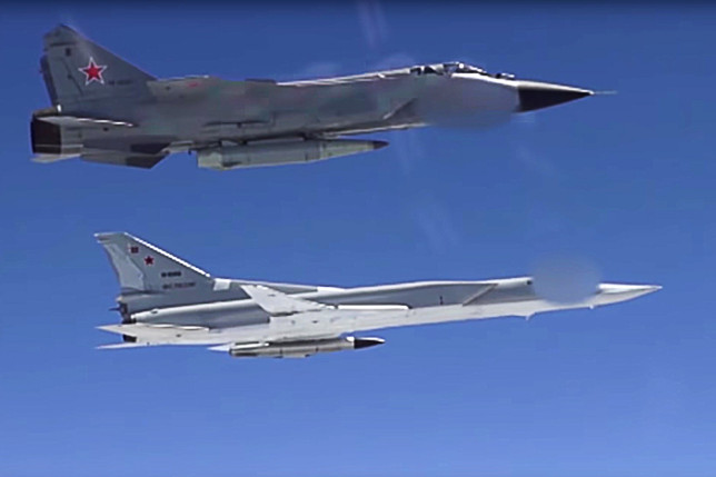 RUSSIA - JULY 19, 2018: Mikoyan MiG-31 supersonic interceptor aircraft with the Kh-47M2 Kinzhal air-launched ballistic missiles during drills with the Tupolev Tu-22M3 supersonic strike bombers. The Kinzhal missile can be launched from Tupolev Tu-22M3 bombers or Mikoyan MiG-31BM interceptors; it accelerates to hypersonic speed and is able to perform sharp maneuvers, which makes it almost invulnerable for any missile defence system. Video screen grab/Press and Information Office of the Defence Ministry of the Russian Federation/TASS