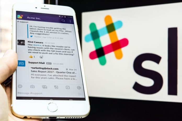 A young man is using an iPhone as he uses Slack