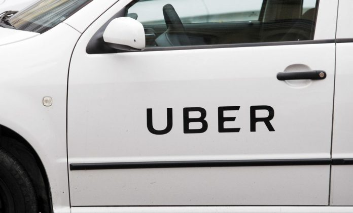 Uber logo is seen on a car's door on the street in Kiev,