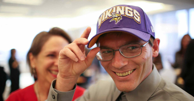 Damon Thibodeaux smiles while wearing a Minnesota Vikings cap.